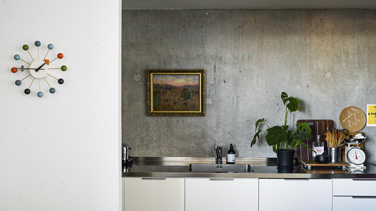 Vaaleassa keittiössä on rosteritasot ja betoniseinä, jolla roikkuu maisemaa kuvaava taulu, jossa on kultaiset kehykset. kuva: Hanna Pielikko